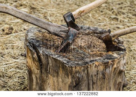 Axe stuck in treeold axe stuck in a stump on a background of straw closeup