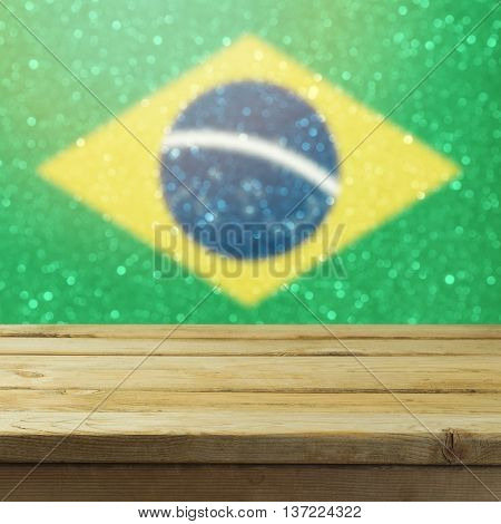 Empty wooden deck table over Brazil flag bokeh background. Ready for product display montage.