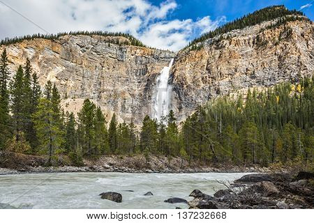Sunny autumn day in Yoho National Park in the Rocky Mountains of Canada. Colossal Takakkaw waterfall formed by melting glacier Daly