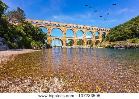 Three-tiered aqueduct Pont du Gard - the highest in Europe. The bridge was built in Roman times on the river Gardon. Above the bridge flies flock of cranes poster