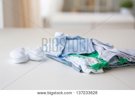 clothing, babyhood, motherhood and object concept - close up of baby bootees and pile of clothes for newborn boy at home