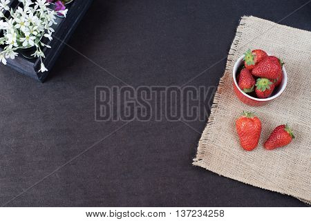 Fresh Strawberries In Mini Metal Bucket On Hessian Jute. White And Purple Flowers In A Decorative Wo