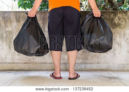 Low section of a young man carrying garbage bags