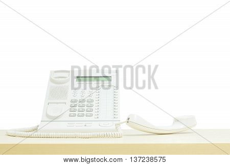 Closeup white phone office phone on blurred wooden desk in the meeting room under window light isolated on white background