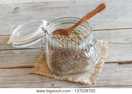 Dry Raw Rye Grain in a jar with a spoon