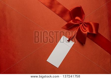 Red Silk Cloth Background with Tag Label and Ribbon Bow Present Pricing Tag Over Fabric Texture
