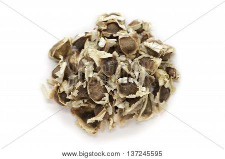Organic Moringa (Moringa oleifera) seeds isolated on white background. Macro close up. Top view.