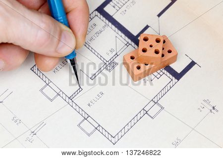 man is drawing a house plan with pencil