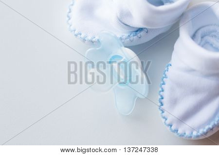 clothing, babyhood, motherhood and object concept - close up of white baby bootees and soother for newborn boy