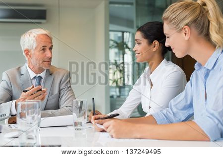 Senior manager giving training to new businesswomen in office. Group of businesspeople working together during a meeting in boardroom. Human resources director talking with new employees.