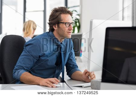 Absorbed businessman working on computer at desk. Focused and serious business man analyzing report at computer in office. Businessman checking emails with computer.