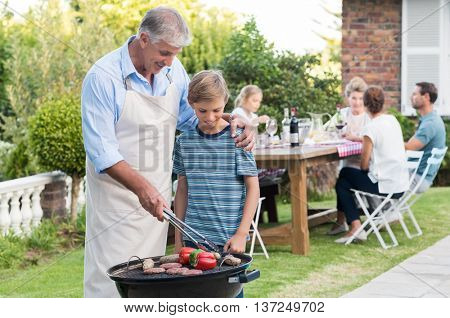 Grandson helping grandfather in barbeque. Happy grandpa teaching grandson how to cook food. Grandson enjoying watching grandfather cooking barbeque.