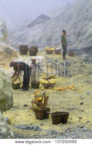 KAWAH IJENINDONESIA-JAN 10:Unidentified miner harvests raw sulphur from the crater of Kawah Ijen volcano in hazardous working environment with minimal protection on JAN 10 2011 in Kawah Ijen