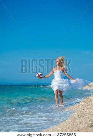 Beautiful young bride walking on the beach on her wedding day