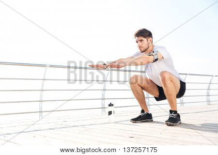 Young handsome sportsman doing squatting exercises outside at the pier