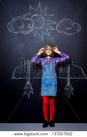 Dream flight. Cheerful girl imagines herself a pilot. Childhood. Fantasy, imagination.