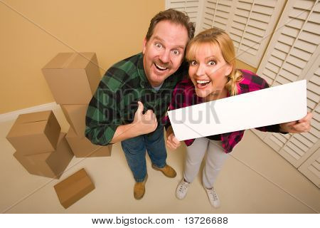 Goofy Thumbs Up Couple Holding Blank Sign in Room with Packed Cardboard Boxes.