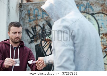Pusher and drug addict exchanging money and drug