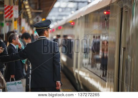 TOKYO JAPAN - NOVEMBER 29 2015: An unidentified Japanese train conductor is on his duty on a platform at Ikebukuro station