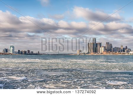 DETROIT MI/USA - JANUARY 29 2016: Icy Detroit River Detroit and Windsor Ontario skylines Ambassador Bridge from Sunset Point in Belle Isle Park. Visible: GM Renaissance Center and Cobo Center.