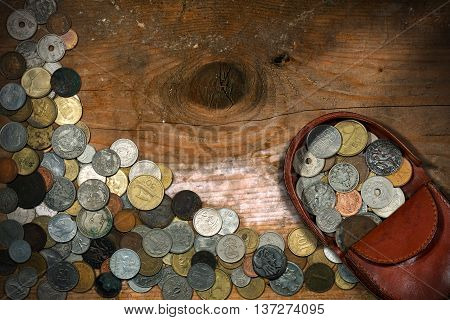 Brown leather coin purse with old and vintage coins. On a wooden table with many antique coins