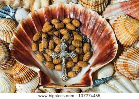 Close up of a wooden rosary beads with a silver crucifix in a scallop seashell. Symbol of Christian pilgrimage
