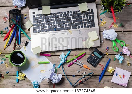 Overhead shot of messy office desk with modern laptop