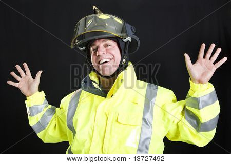 Firefighter lets off steam by goofing around.  Photographed on black background.