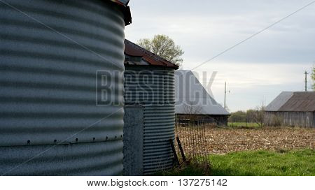 Duo of grain bins on farm setting