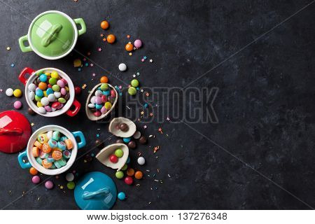 Colorful candies and lollypops on stone background. Top view with copy space