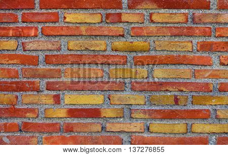 New red brick wall of rustic bricks of different length.