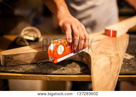 Man is making gutar using laser intrument.