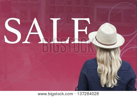 Woman in front of shop window with sale