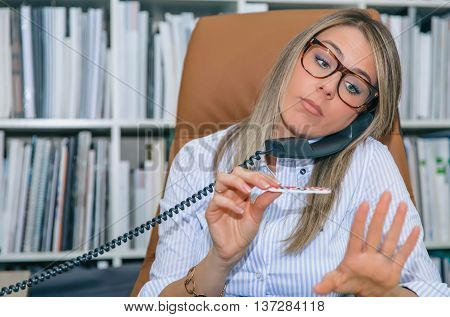 Close up of unmotivated blonde secretary polishing nails at workplace while talking on phone