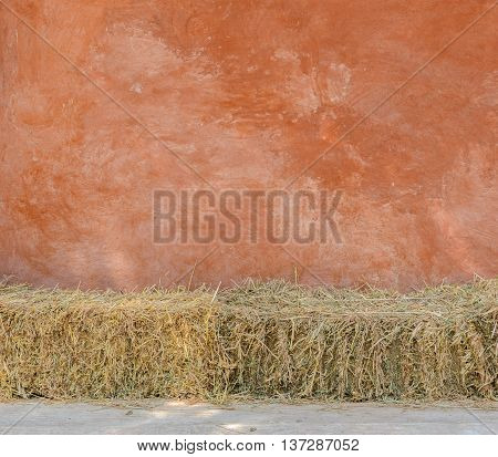 Red natural wall texture of cob house with straw bales as a seat. It is a natural building material made from subsoil water and straw fibrous organic material.