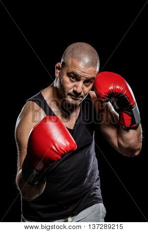 Portrait of boxer performing uppercut on black background