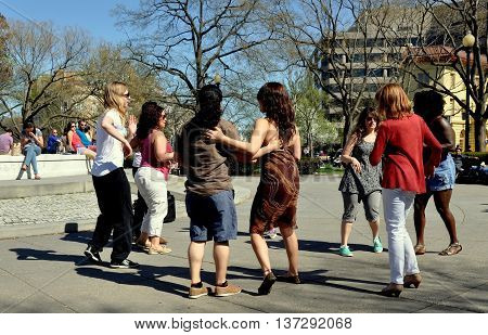 Washington DC - April 12 2014: Group of young people Salsa dancing on the plaza at Dupont Circle on a warm Spring afternoon