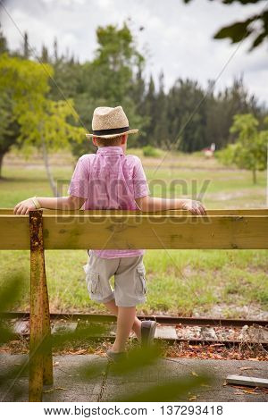 Cute kid boy in s a straw hat standing on either side of an old rail fence. Child stands leaning on the fence at the railway station and waiting for a train on a summer day. Outdoors.