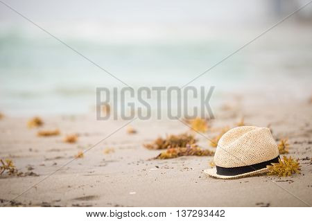 Nice straw hat laying on the sand. Beautiful ocean beach background. Outdoors. Vacation time. End of summer vacations. Dreaming of holidays by the sea. Traveling.