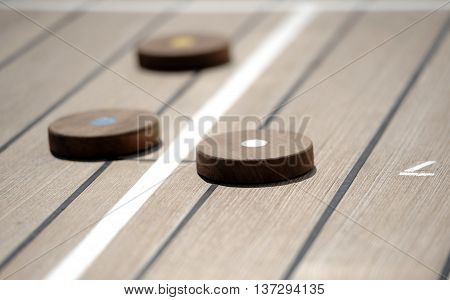 Shuffleboard game on the wooden deck of a cruise ship
