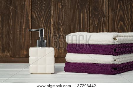 Still life white soap dispenser with stacked towels on dark and light wood. Closeup background with space for text.