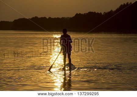 Silhouette boy on sup-board stand up paddle board