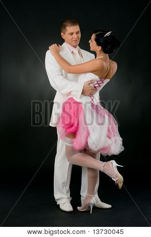 Wedding couple cuddling. Bride wearing tied up, pink and white wedding dress and sexy stockings.?