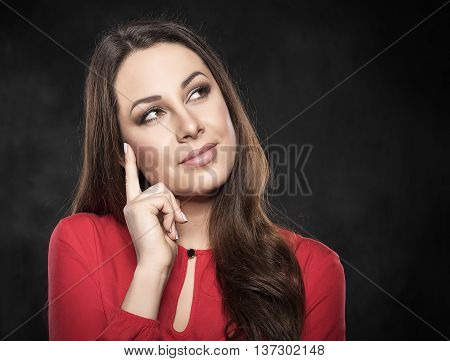 serious young woman pondering over something on a dark background. There is a free space for text or image.