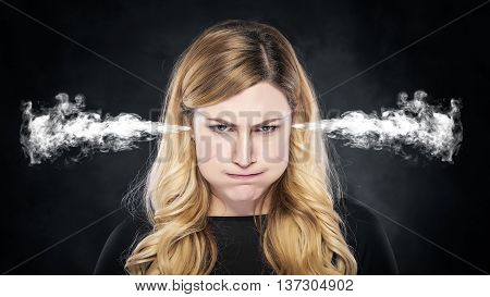 Steam or smoke from the ears of the woman over dark background.