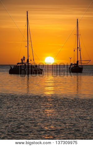Vivid gold orange sunset over ocean. Large white sun on horizon in Caribbean. Man and woman stand on a boat in silhouette. Colorful golden sky, cloud streaks in St Lucia. Reflection of boats in sea.
