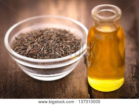 Caraway seeds with essential oil in glass bottle on wooden surface