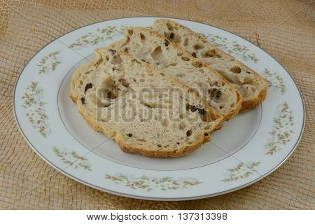 Kalamata olive bread slices on white plate on burlap
