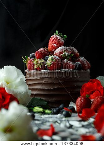 Ripe strawberries in a chocolate cake on a black background