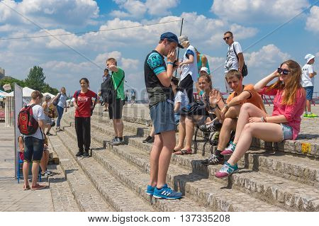 DNEPR UKRAINE - June 25 2016:Group of positive young people having rest on the Dnepr river embankment at June 25 2016 in Dnepr Ukraine
